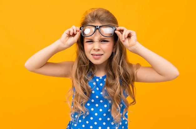 Écolière avec des lunettes lève des lunettes sur ses yeux, mal voir l'enfant