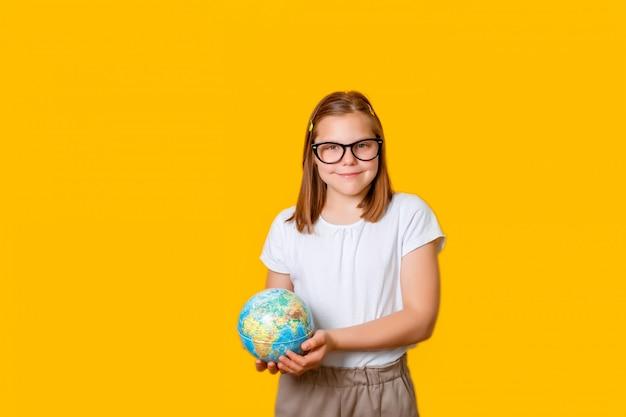 Une écolière avec des lunettes tient un globe dans ses mains
