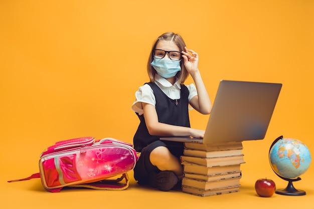 Une écolière en masque médical est assise derrière une pile de livres et d'ordinateurs portables pour l'éducation des enfants en cas de pandémie