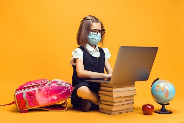 Une écolière en masque médical est assise derrière une pile de livres travaille sur l'éducation des enfants sur ordinateur portable en cas de pandémie