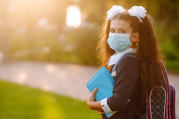 Écolière en masque médical protecteur au coucher du soleil. quarantaine face au covid19.