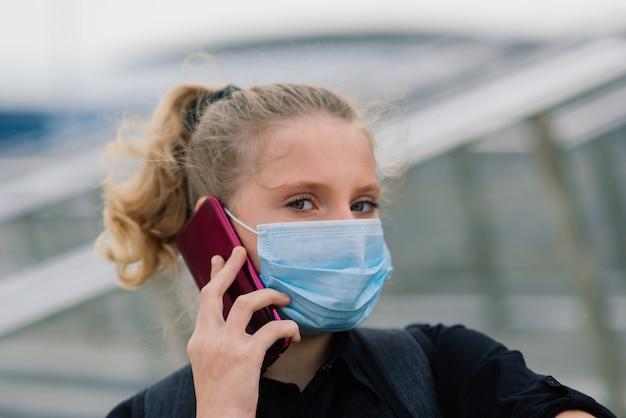 Écolière en masque médical de protection au coucher du soleil. élève moderne avec un sac à dos pendant la quarantaine covid-19.