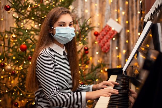 Écolière en masque médical à la recherche de l'appareil photo tout en jouant du piano
