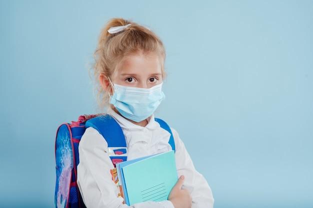 Écolière avec masque médical et sac à dos a des cahiers et des livres à la main isolés sur fond bleu