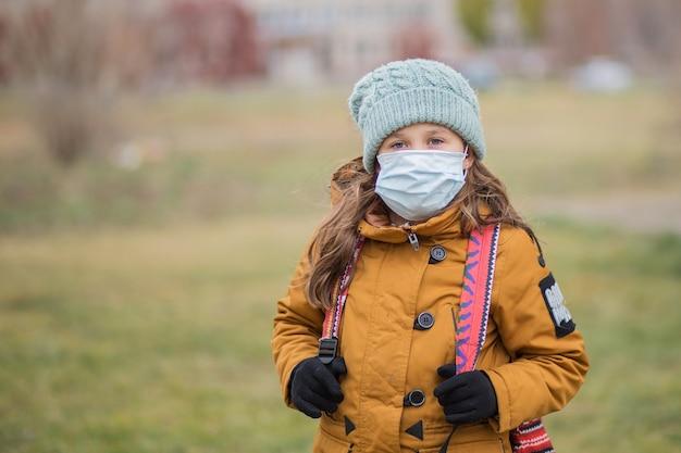 Écolière en masque médical avec sac à dos