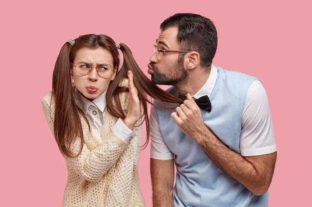 Une écolière mécontente et agacée ne montre aucun signe, refuse de recevoir le baiser de son camarade de classe wonk
