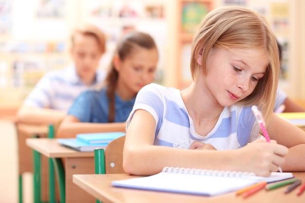 Écolière mignonne en classe sur leçon