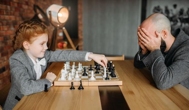 Écolière mignonne jouant aux échecs avec une personne de sexe masculin adulte.