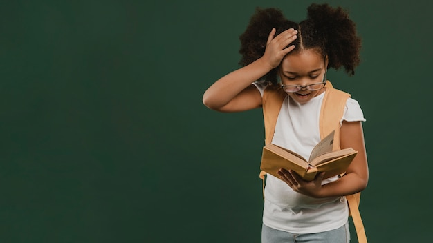 Écolière mignonne lisant un livre