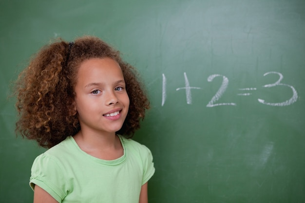 Écolière mignonne posant devant une addition