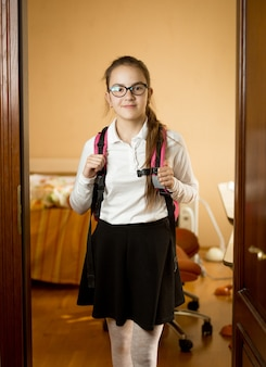Écolière mignonne avec sac à dos sortant de sa chambre à l'école