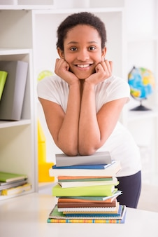 Écolière mulâtre debout avec une pile de livres.