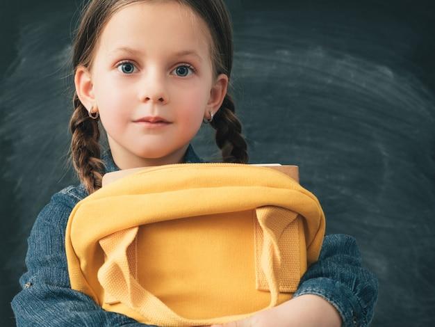 Écolière avec des nattes portant dos jaune avec des livres