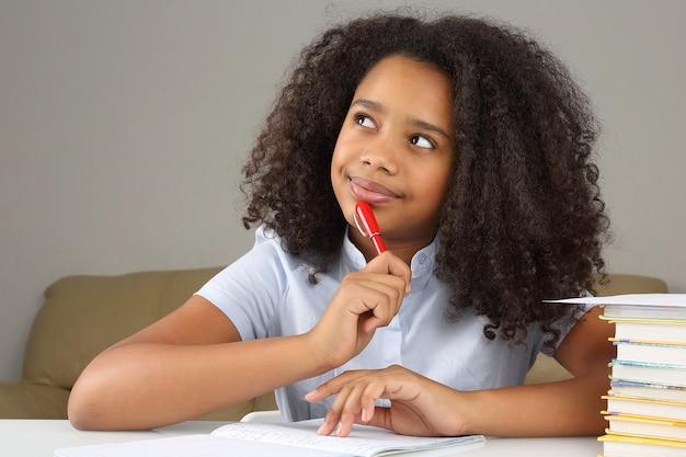 Une écolière noire pense aux devoirs scolaires