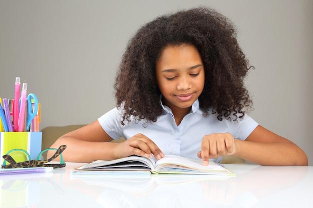Écolière à la peau sombre, lisant un livre à faire ses devoirs