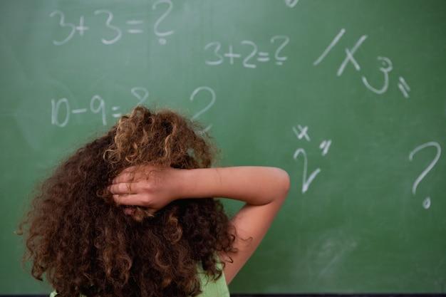 Écolière en pensant aux mathématiques tout en grattant le dos