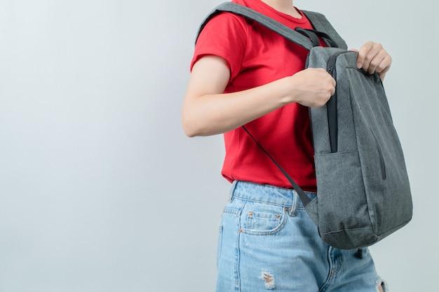 Écolière portant son sac à dos gris aux épaules.