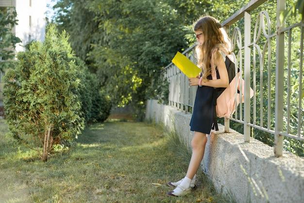 Écolière, porter, lunettes, à dos, lecture, cahier
