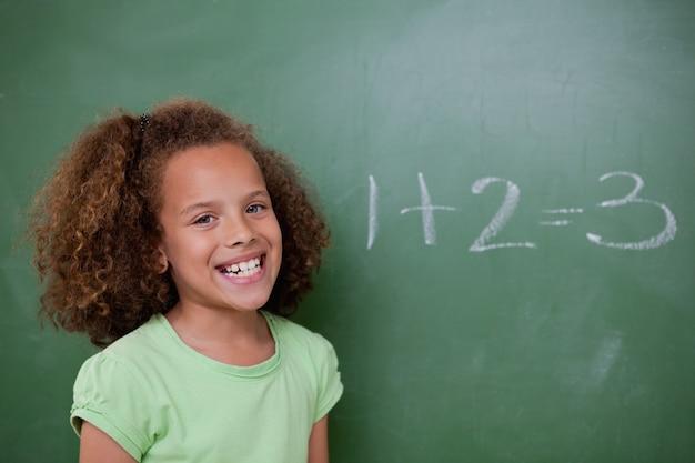 Écolière posant devant un ajout sur un tableau noir