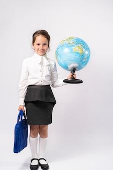 Écolière de première année dans une chemise blanche tient un globe dans ses mains et pleure