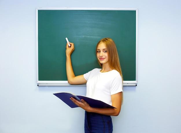 Écolière près du tableau noir, tableau noir. étudiant écrit
