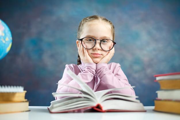 Écolière primaire tenir la tête dans la main étude photo