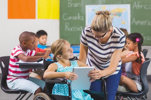Écolière et professeur à l'aide de tablette numérique en classe