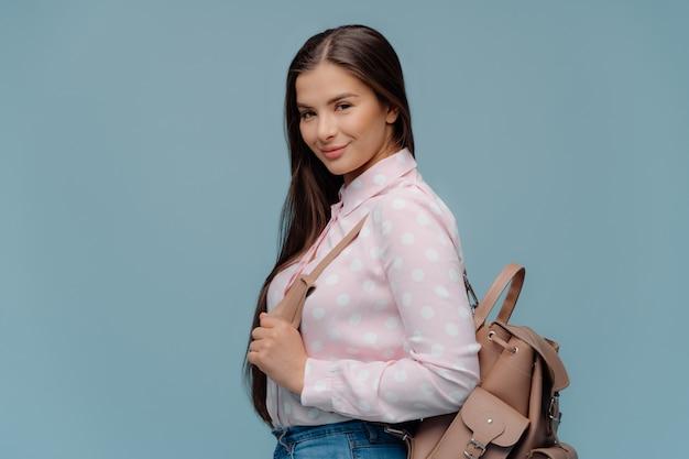 Écolière ravie à la mode porte un sac à dos
