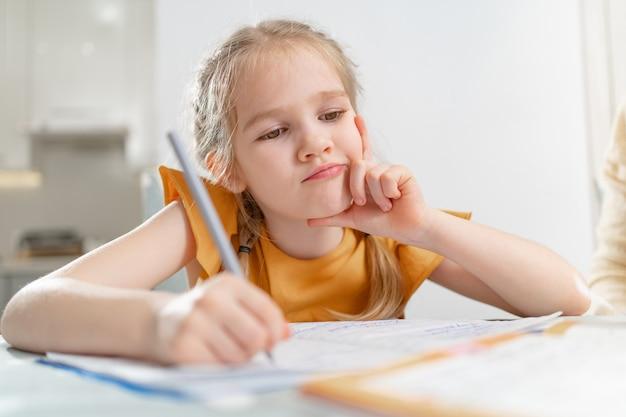 Écolière réfléchie fait ses devoirs. complexités d'une écriture correcte et belle.