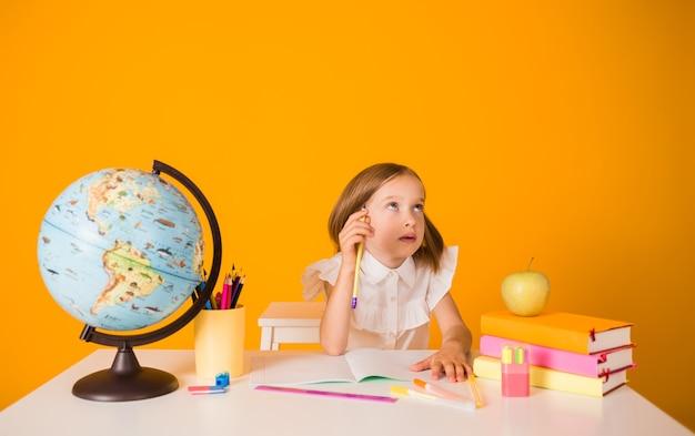 Une écolière réfléchie en uniforme est assise à une table avec des fournitures scolaires sur fond jaune avec une place pour le texte