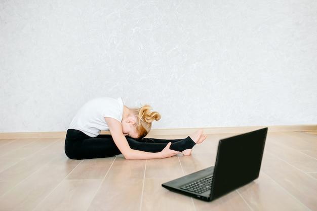 Écolière regardant une vidéo en ligne sur un ordinateur portable et faisant des exercices sportifs - yoga, gymnastique, chorégraphie. reste à la maison. concept d'auto-isolement, de quarantaine, d'éducation en ligne.