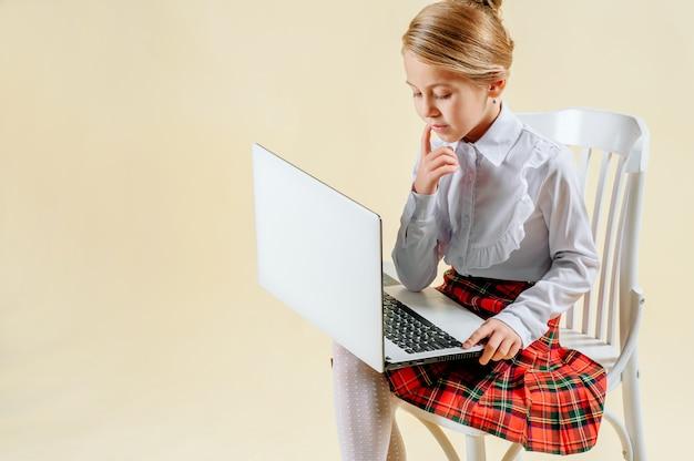 Écolière regarde l'ordinateur portable