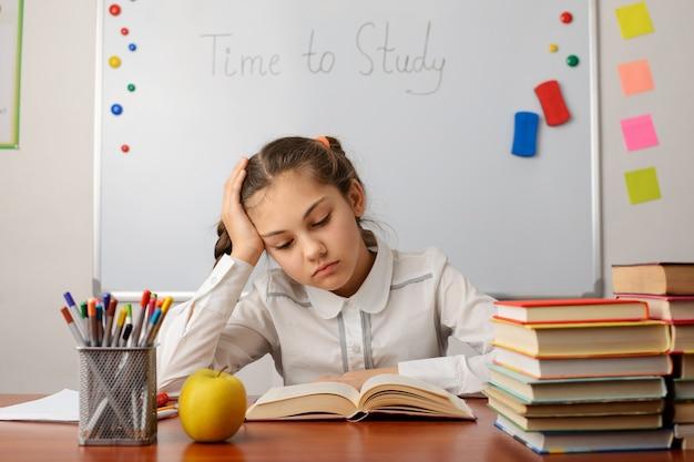 Une écolière s'ennuie, lisant un livre, ne veut pas étudier