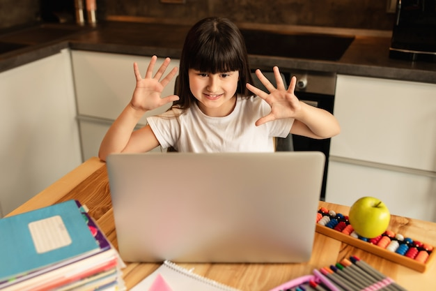 Écolière s'est lavé les mains avec un désinfectant avant de commencer une leçon en ligne et montre ses mains à un enseignant
