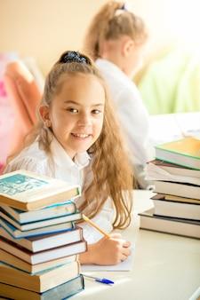 Écolière souriante assise dans la bibliothèque et faisant ses devoirs