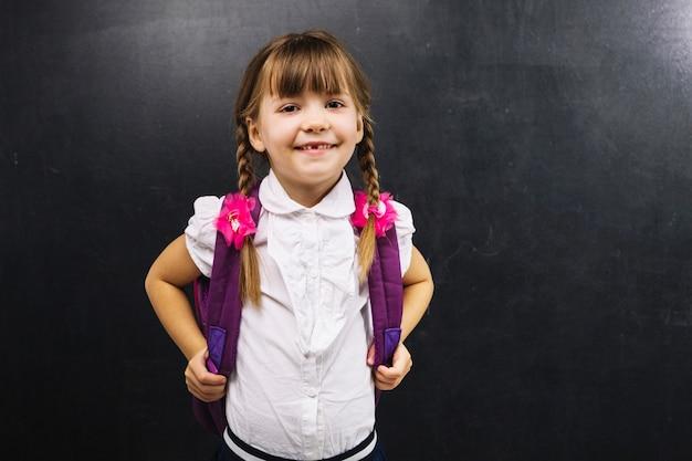 Écolière souriante au tableau noir