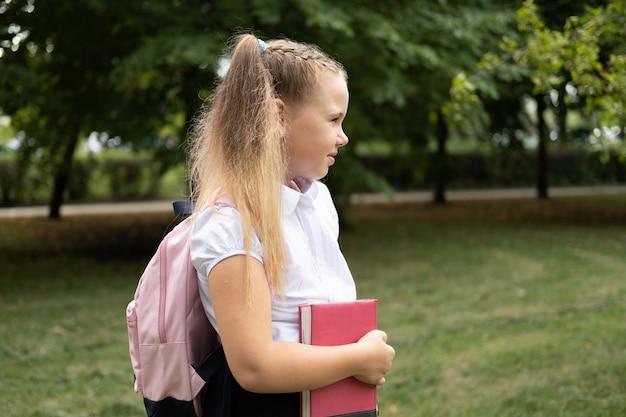Écolière souriante blonde en uniforme scolaire tenant un cahier avec un sac à dos rose retour à l'école en plein air.