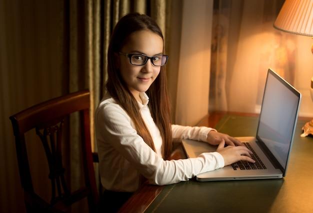 Écolière souriante brune posant dans le cabinet avec ordinateur portable