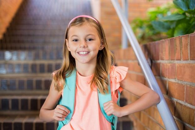 Écolière souriante debout sur l'escalier