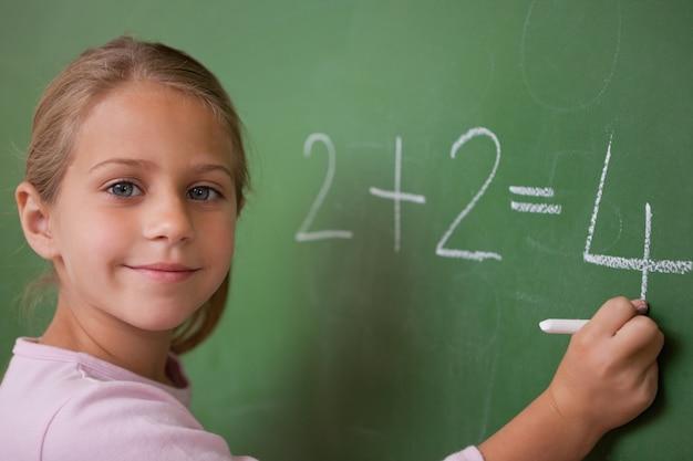 Écolière souriante écrivant un nombre
