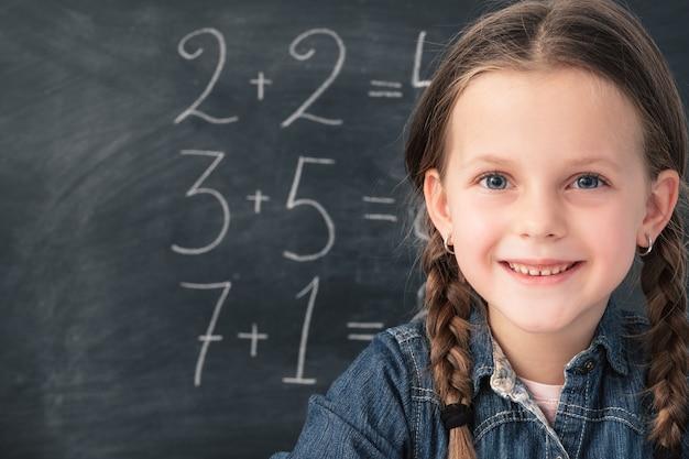 Écolière souriante avec des nattes. sommes mathématiques sur tableau noir derrière elle