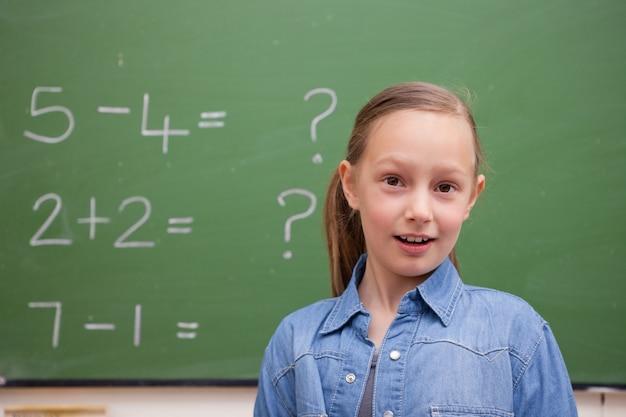 Écolière souriante posant devant un tableau noir