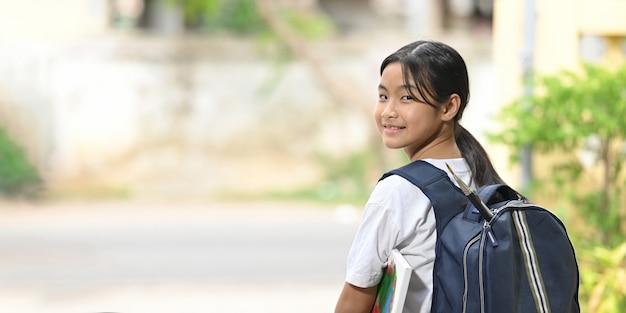 Une écolière tient du matériel de peinture et porte un sac d'école en se tenant debout et en attendant un autobus scolaire.