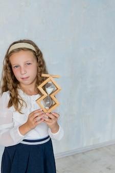 Une écolière tient un sablier dans une salle de classe petite fille dans l'éducation et le sch...