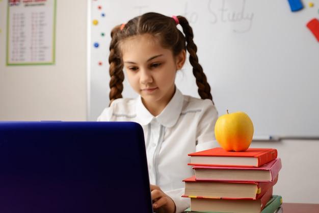 Écolière travaillant sur l'ordinateur portable dans la salle de classe