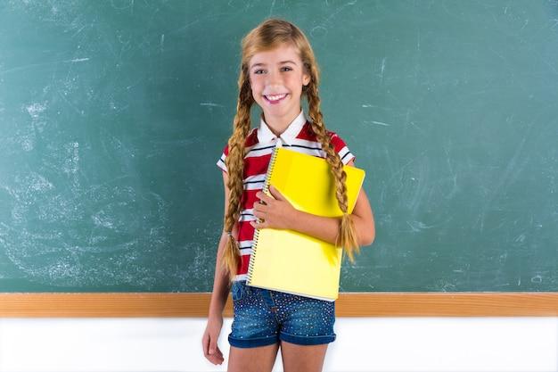 Écolière tresse blonde avec cahier à spirale étudiant