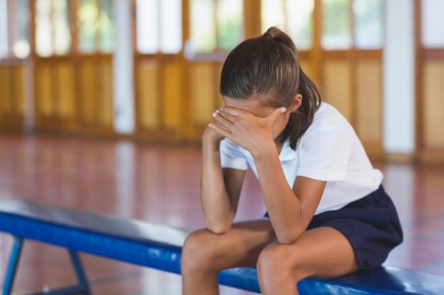 Écolière triste assis seul dans un terrain de basket