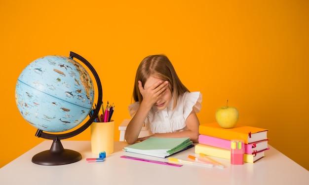 Une écolière triste en blouse blanche est assise à une table avec des fournitures scolaires et un globe et se couvre les yeux de sa main sur fond jaune avec une copie de l'espace