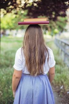 Écolière en uniforme debout dans le jardin avec livre sur la tête
