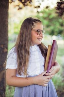 Écolière en uniforme debout dans le jardin avec des livres